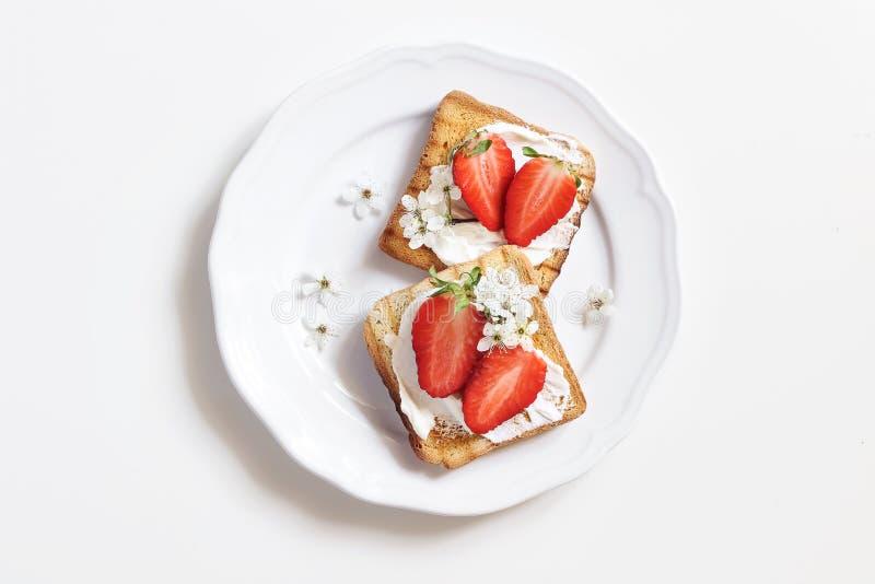 Pan tostado con el queso cremoso, las fresas y las flores de cerezo en la placa de la porcelana Fondo de madera de la tabla Prima imágenes de archivo libres de regalías