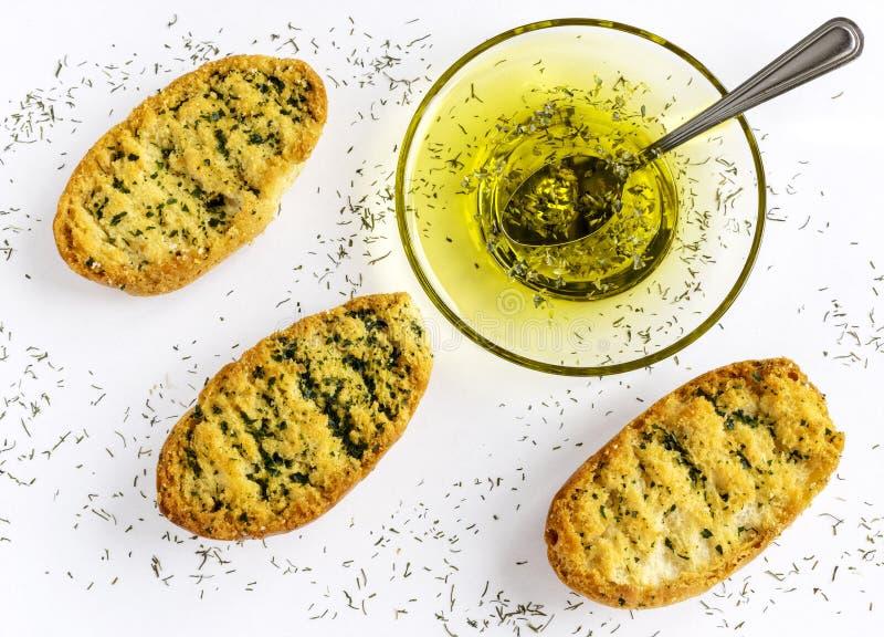 Pan tostado con las hierbas y el aceite de oliva en el pan de ajo tostado Fondo blanco foto de archivo