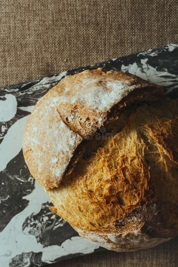 Pan tradicional recientemente cocido en la tabla de mármol blanco y negro imagen de archivo libre de regalías