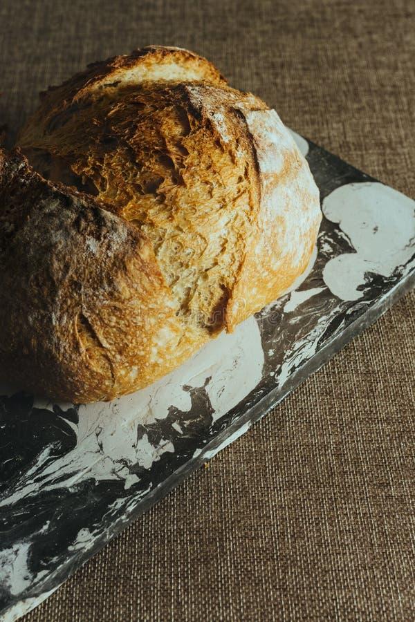 Pan tradicional recientemente cocido en la tabla de mármol blanco y negro imágenes de archivo libres de regalías