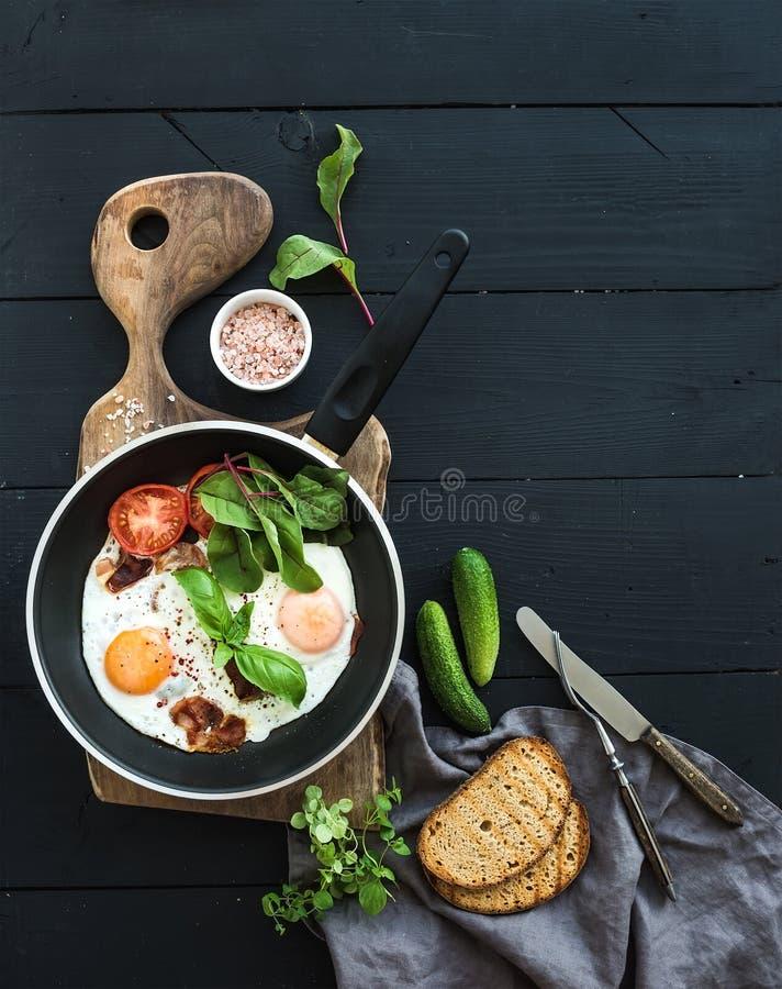 Pan van gebraden eieren, bacon, tomaten met brood royalty-vrije stock foto's