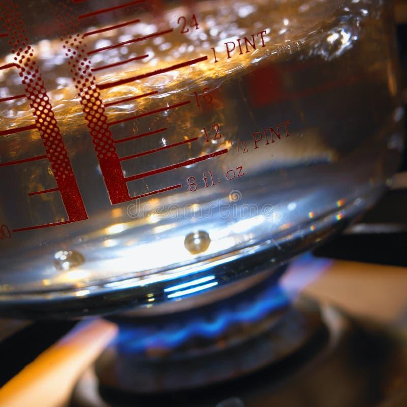 Pan van kokend water op de haardplaat van het gaskooktoestel stock foto
