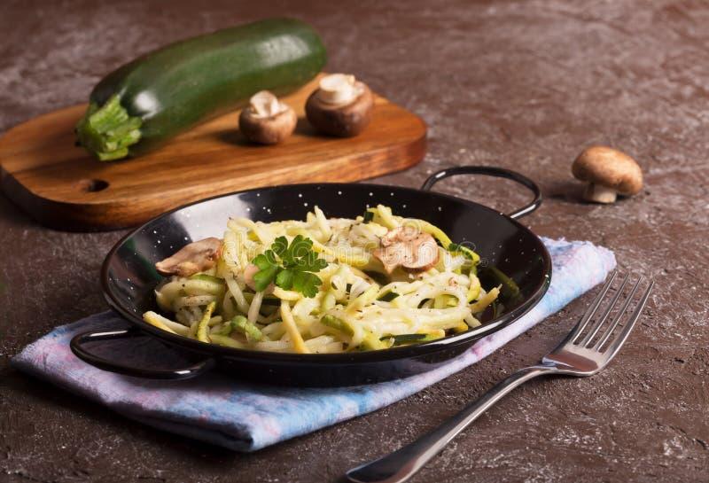Pan van spaghetti van courgette en paddestoelsaus op houten lijst wordt voorbereid die stock afbeelding