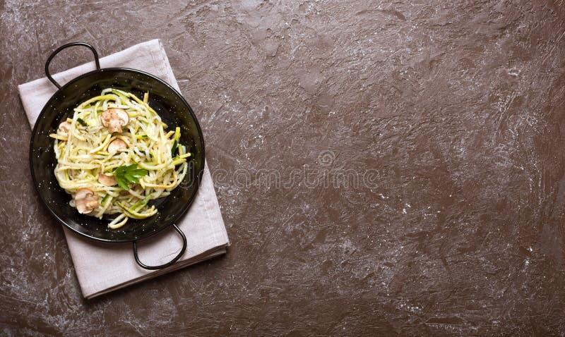 Pan van spaghetti van courgette en paddestoelsaus op houten lijst wordt voorbereid die royalty-vrije stock fotografie