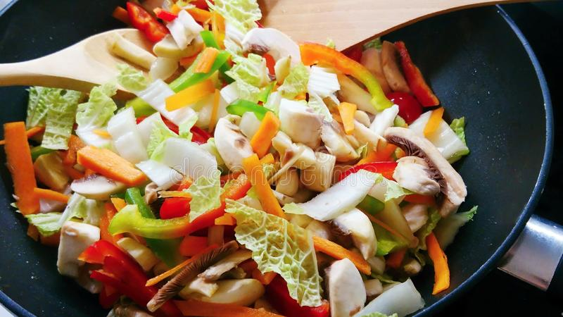 Pan of vegetable stir-fry. Closeup of pan with fresh vegetable stir-fry and wooden spoons stock photo