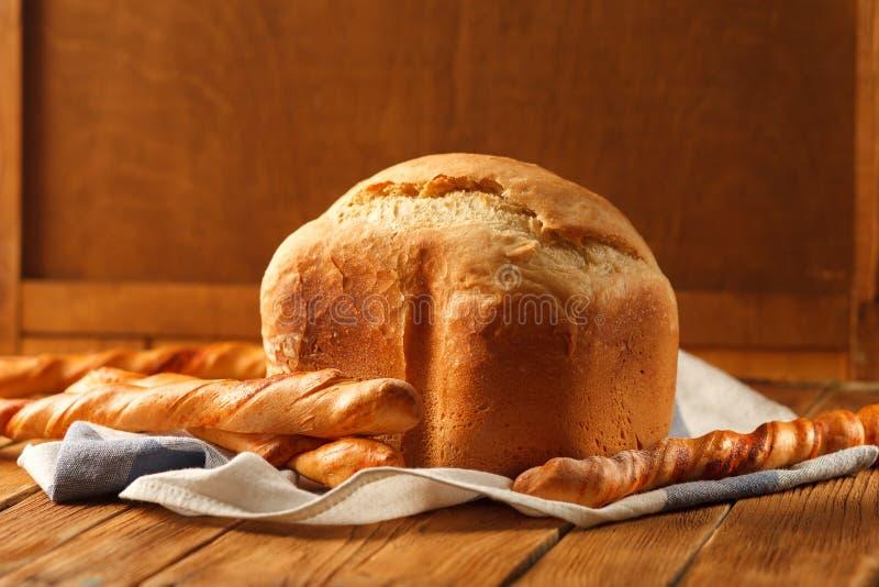 Pan y baguettes franceses en la tabla de madera rústica imagenes de archivo