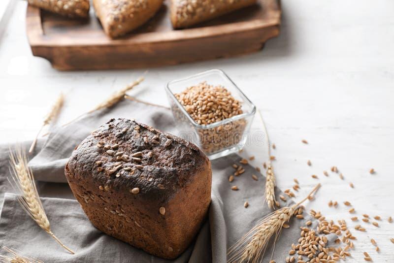 Pan y cuenco sabrosos frescos con los granos del trigo en la tabla fotografía de archivo