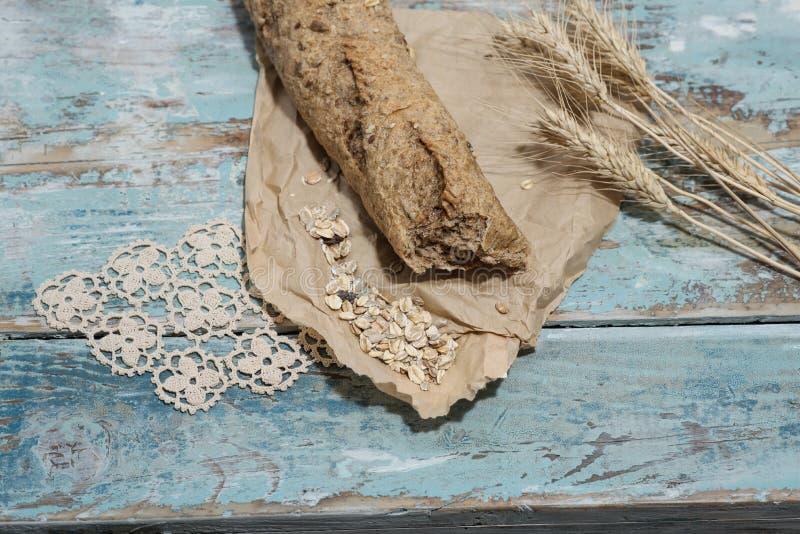 Pan y muesli llenos del grano en un tablero de madera imagen de archivo