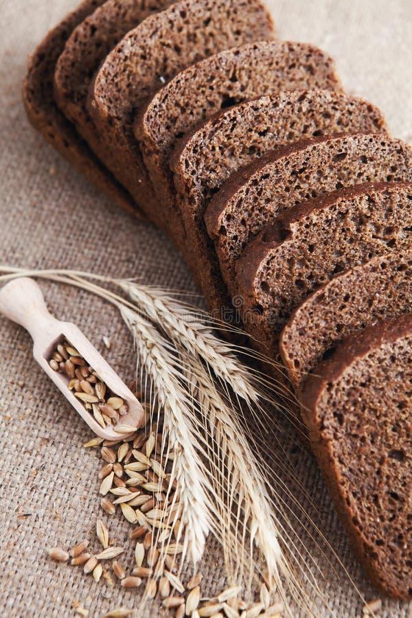 Pan y oídos cortados del trigo en fondo de la lona imagen de archivo libre de regalías