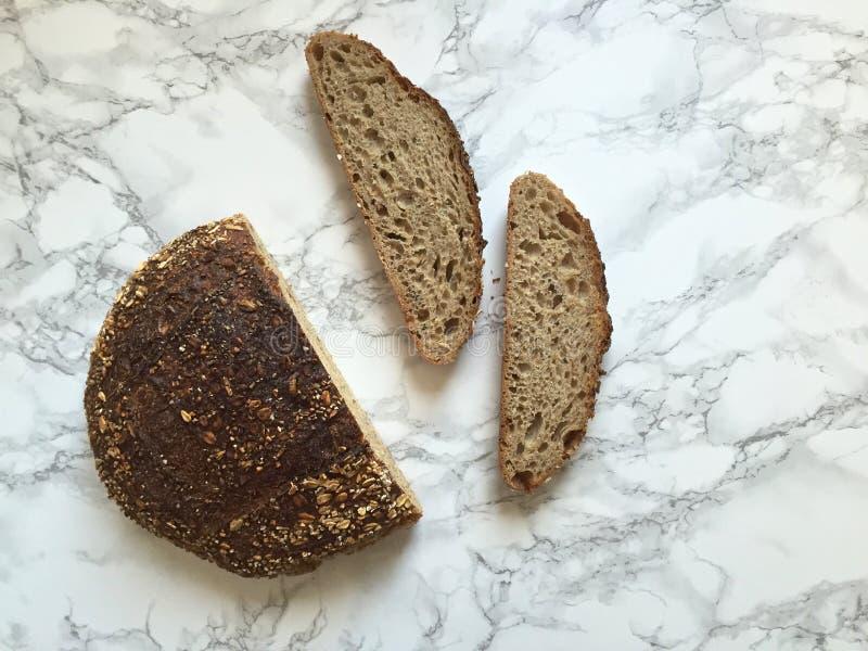 Pan y rebanadas artesanales del pan del pan amargo en la encimera de mármol fotografía de archivo