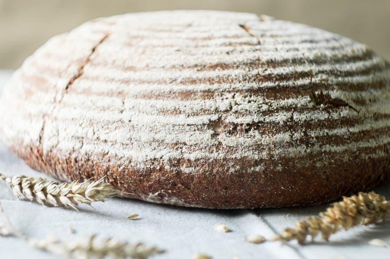 Pan y trigo del artesano del pan amargo en la toalla de cocina fotografía de archivo