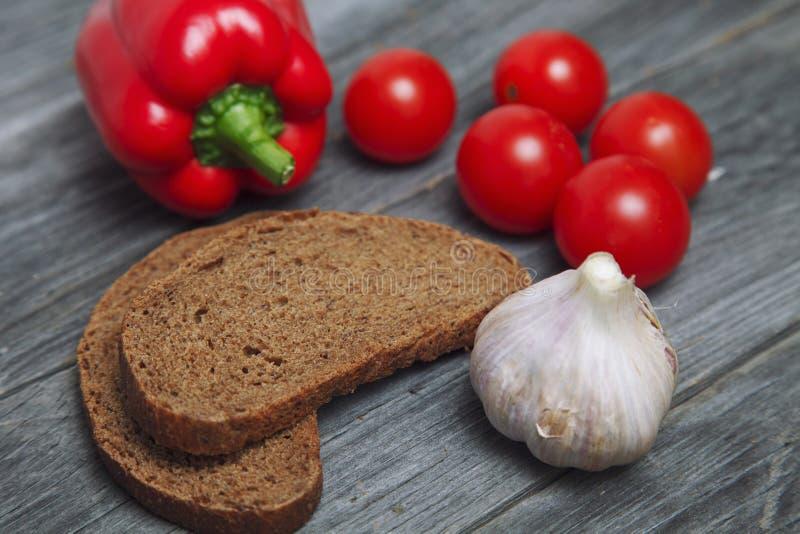 Pan y verduras cereza y ajo del tomate de la pimienta en de madera fotografía de archivo