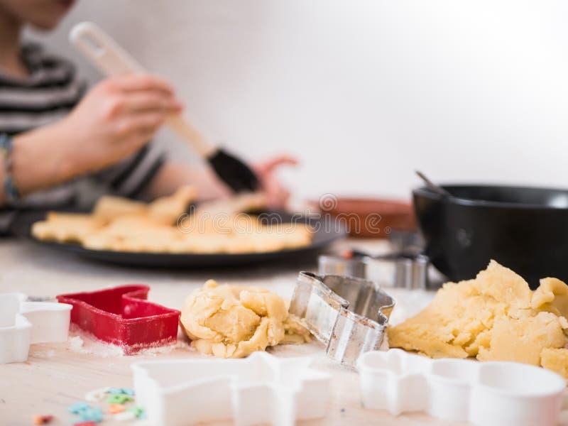 Panadería de la Navidad: Pasta de la galleta de la pintura de la niña con el satinado del azúcar fotos de archivo libres de regalías
