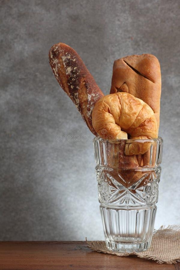 Panadería del clavito del cruasán en el soplo de cristal en la tabla del teakwood foto de archivo