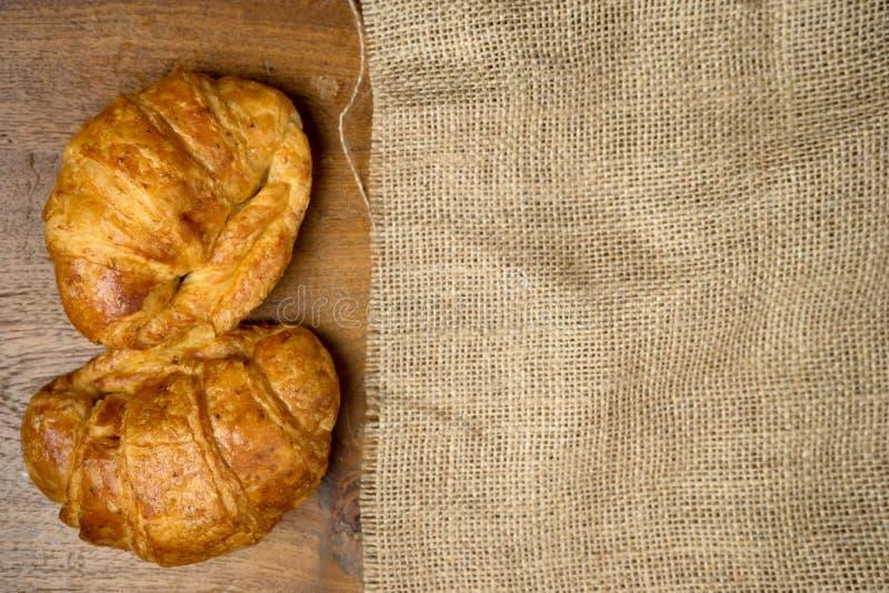 Panadería del cruasán en la tabla de madera de la teca de la arpillera imagen de archivo