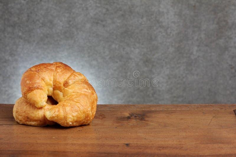 Panadería del cruasán en la tabla del teakwood imagenes de archivo