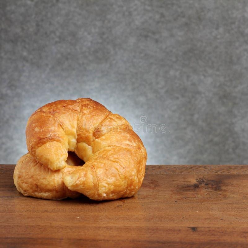 Panadería del cruasán en la tabla del teakwood imagen de archivo