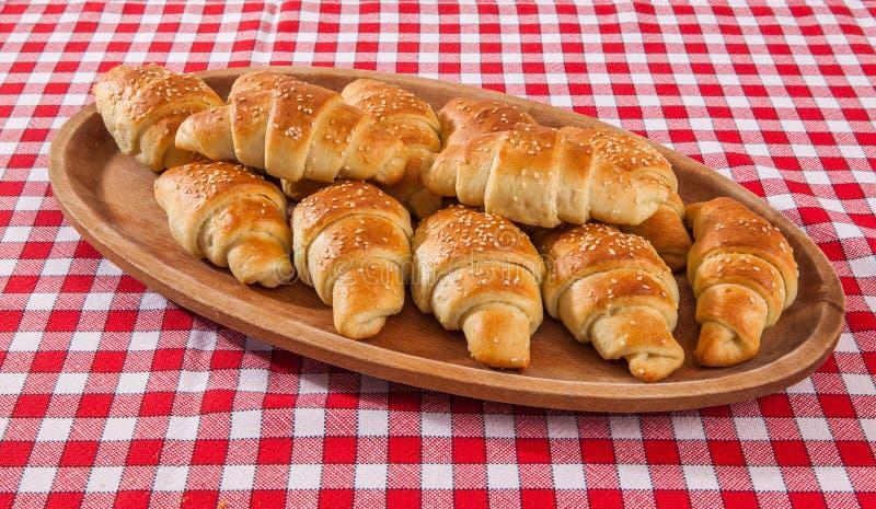 Panadería del cruasán en la tabla del teakwood en backgr rojo y blanco de la fibra fotografía de archivo