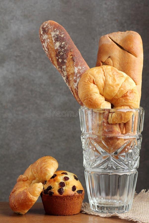 Panadería del mollete del clavito del cruasán en el soplo de cristal en la tabla del teakwood imágenes de archivo libres de regalías