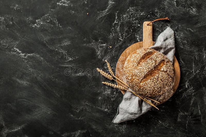 Panadería - pan redondo del pan rústico en fondo negro imagenes de archivo