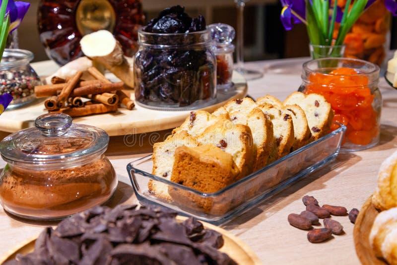 Panadería y bocados del primer, frutas secadas y nueces en los bol de vidrio, canela, placa con biscotti de la pasa Lujo del degu foto de archivo