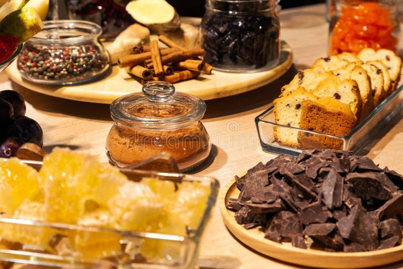 Panadería y bocados, frutas secadas, pedazos queso parmesano, panales, chocolate oscuro, palillos de canela, biscotti del primer  fotografía de archivo libre de regalías
