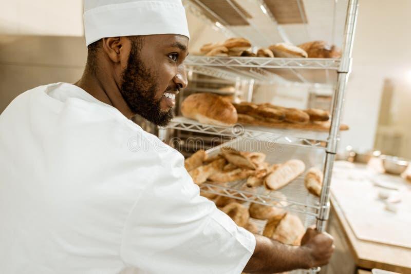 panadero afroamericano feliz que conduce estantes del pan fresco foto de archivo libre de regalías