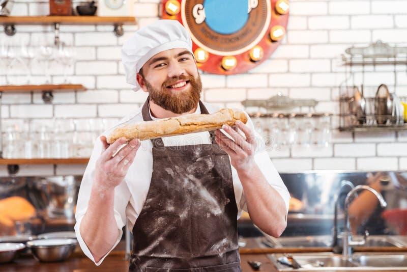 Panadero alegre que muestra la barra de pan en la cocina foto de archivo