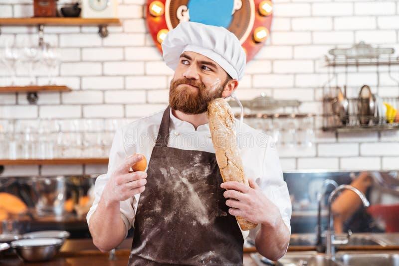 Panadero barbudo pensativo que sostiene los huevos y el pan en la cocina foto de archivo