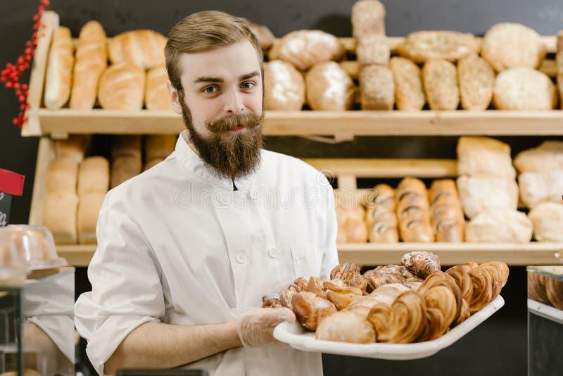 Panadero carismático con una barba y soportes del bigote con una bandeja con los pasteles frescos en el fondo de estantes con imagen de archivo libre de regalías