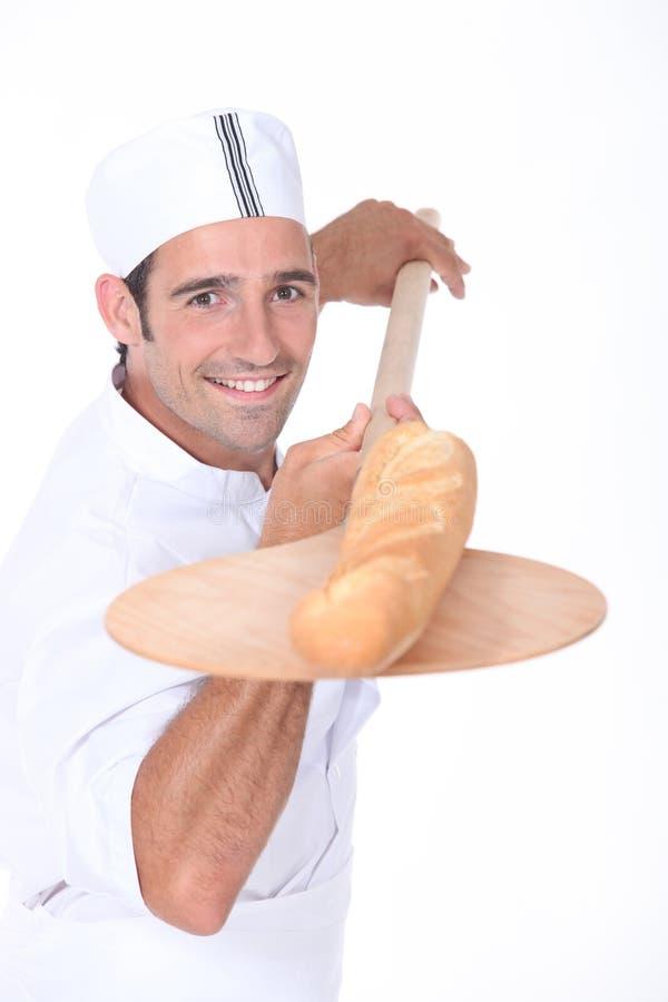 Panadero con el baguette recientemente cocido hacia fuera del horno foto de archivo