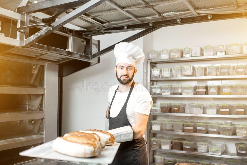 Panadero con panes cocidos en la panadería fotos de archivo libres de regalías