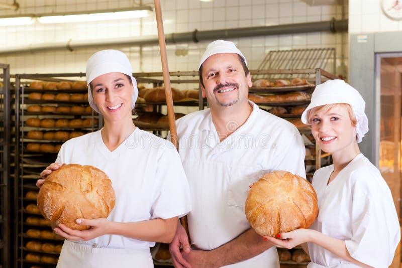 Panadero con sus personas en panadería imagenes de archivo