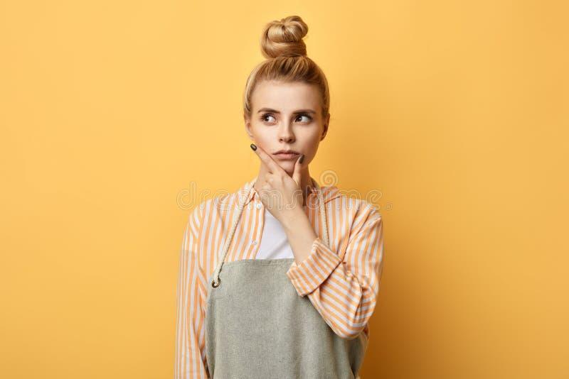 Panadero de sexo femenino con la palma en su barbilla que mira a un lado, encima de fotografía de archivo