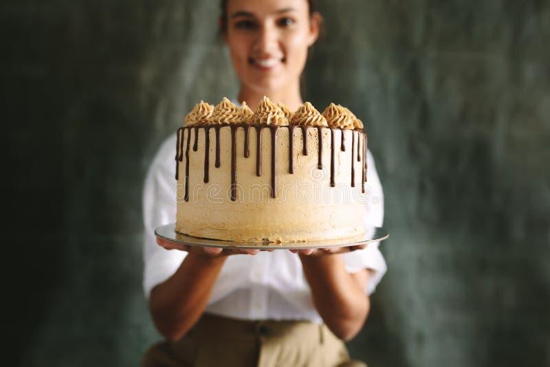 Panadero de sexo femenino con una torta deliciosa foto de archivo
