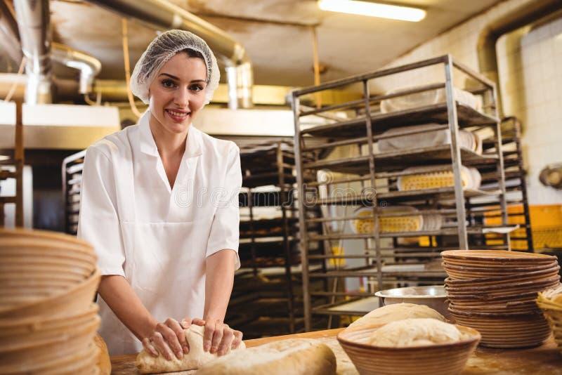 Panadero de sexo femenino que amasa una pasta imagen de archivo