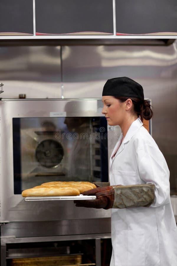 Panadero de sexo femenino serio con los baguettes foto de archivo libre de regalías