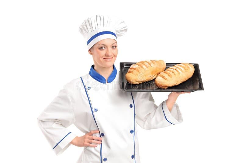 Panadero de sexo femenino sonriente que muestra los panes recientemente cocidos al horno foto de archivo libre de regalías