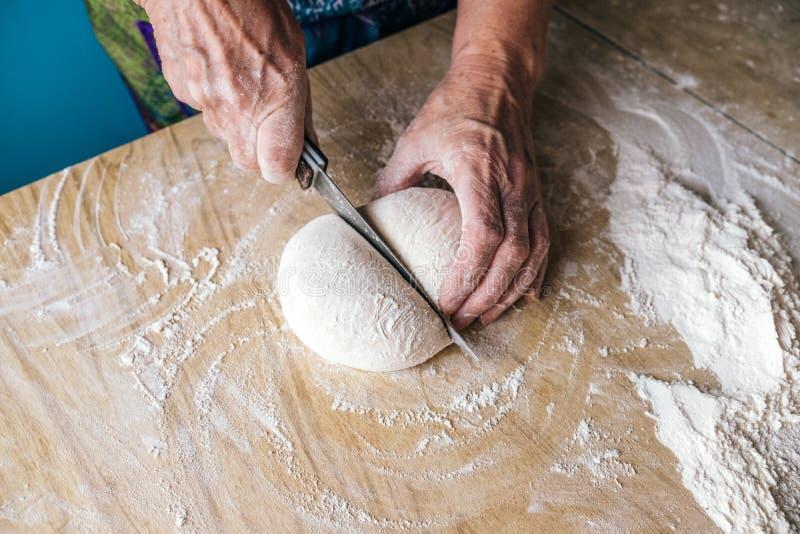 Panadero de una más vieja mujer que corta la pasta en la cocina casera imágenes de archivo libres de regalías