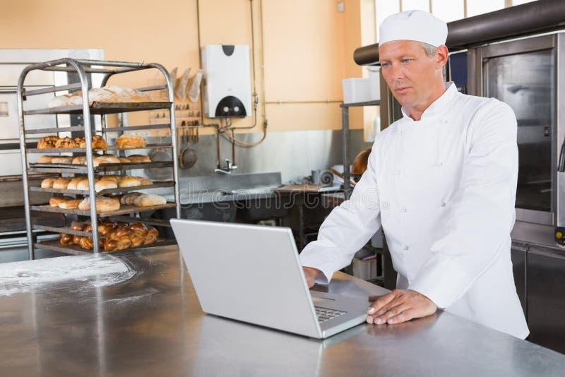 Panadero enfocado que usa el ordenador portátil en worktop foto de archivo libre de regalías