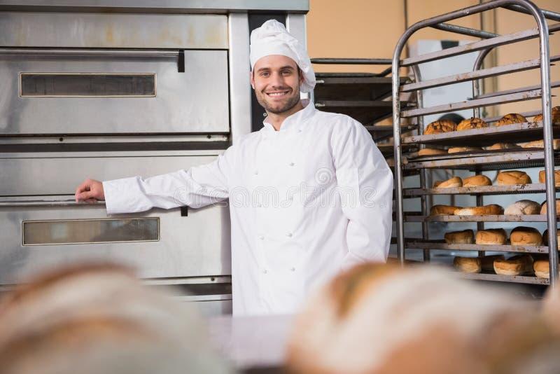 Panadero feliz que se inclina en el horno profesional foto de archivo libre de regalías