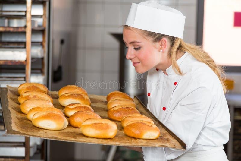 Panadero o aprendiz en la panadería que huele el pan fresco y los bollos imagen de archivo libre de regalías
