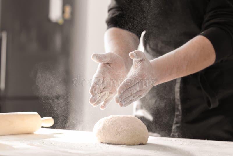 Panadero que asperja la harina sobre la pasta en la tabla de cocina fotos de archivo