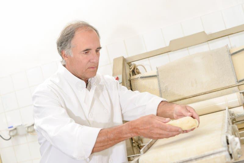Panadero que coloca la pasta sobre transportador imagenes de archivo