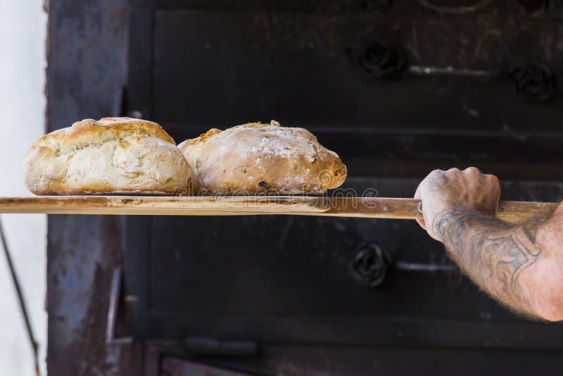 Panadero que cuece el pan hecho a mano fresco en la panadería foto de archivo libre de regalías