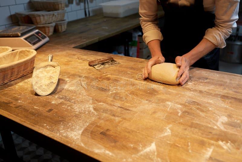 Panadero que hace la pasta de pan en la cocina de la panadería imágenes de archivo libres de regalías