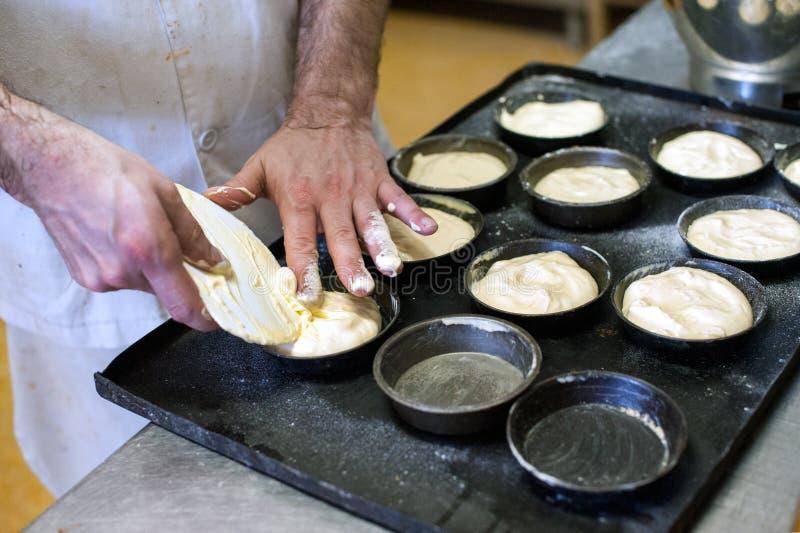 Panadero que hace los pasteles en una panadería imagen de archivo libre de regalías