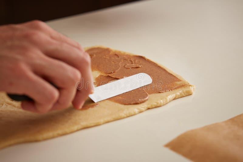 Panadero que pone la crema del canela en la pasta del bollo de leche imagenes de archivo