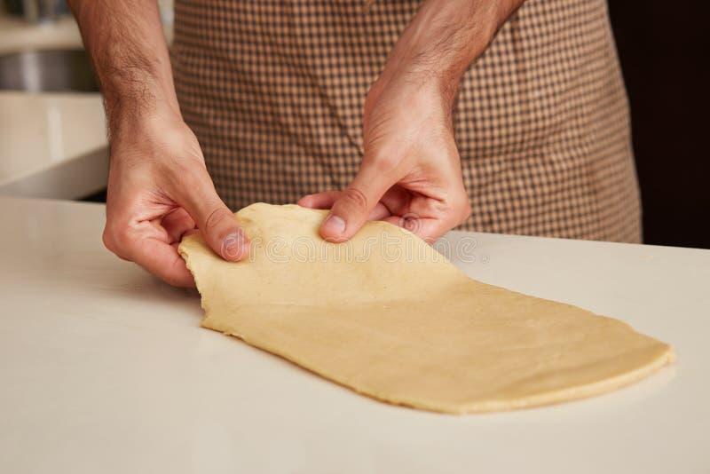 Panadero que prepara la pasta del bollo de leche imagen de archivo