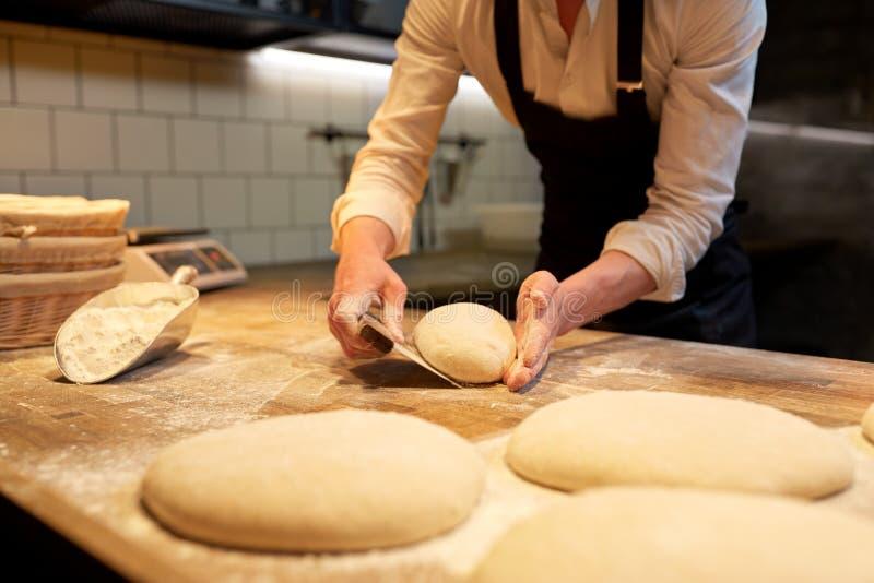 Panadero que reparte la pasta con el cortador del banco en la panadería imagenes de archivo